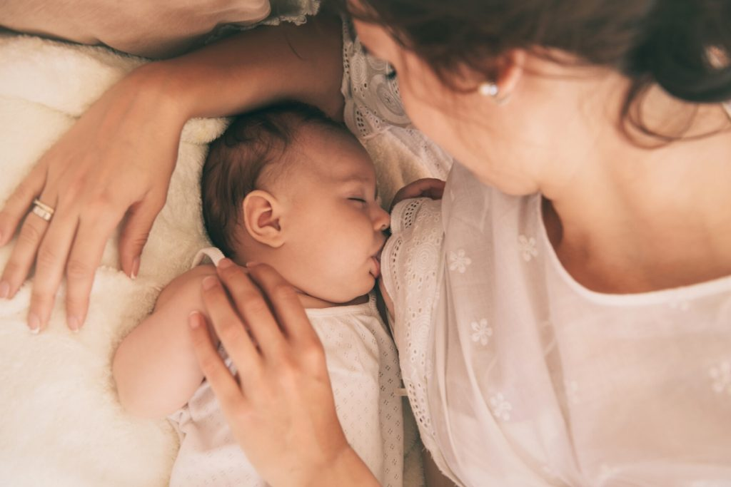 Woman laying on a bed with her new born baby breastfeeding